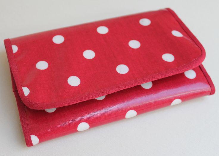 """Peněženka """"Dots in red"""" Peněženka většího formátu opět puntíkatá. Svrchní strana je ze balvněné látky opatřené PVC, takže je otěruvzdorná a dobře se udržuje. Zapínání je na suchý zip. Barva je spíše tmavší červená. Z levé strany je sloupec kapsiček na karty - vejde se 6 karet, z boku pod kapsička na karty je další kapsa a opět další kapsa avšak do ní je ..."""