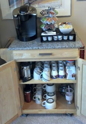Simple buffet turned coffee bar. Clears out a TON of cabinet and counter space, plus keeps all of your coffee and tea stuff together!  Keurig/K-Cups/Splenda/Creamer on top.  Cocoa mixes and flavored creamers in top drawer.  Coffee appliances (grinder, frother, french press) and daily coffee/tea mugs on top shelf.  Travel mugs, specialty/holiday mugs, and travel cups on bottom shelf.