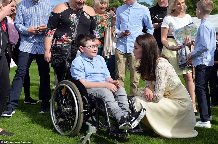 Pictured, Kate talks to a guest at the garden party at Buckingham Palace as his family look proudly on. After the guests were entertained by Jess Glynne and Nina Conti, RAF parashooters landed in the palace grounds