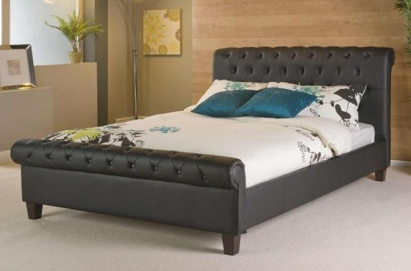 The Phoenix is a stunning black faux leather bed with a rounded headboard and footboard with rounded edges and button details.