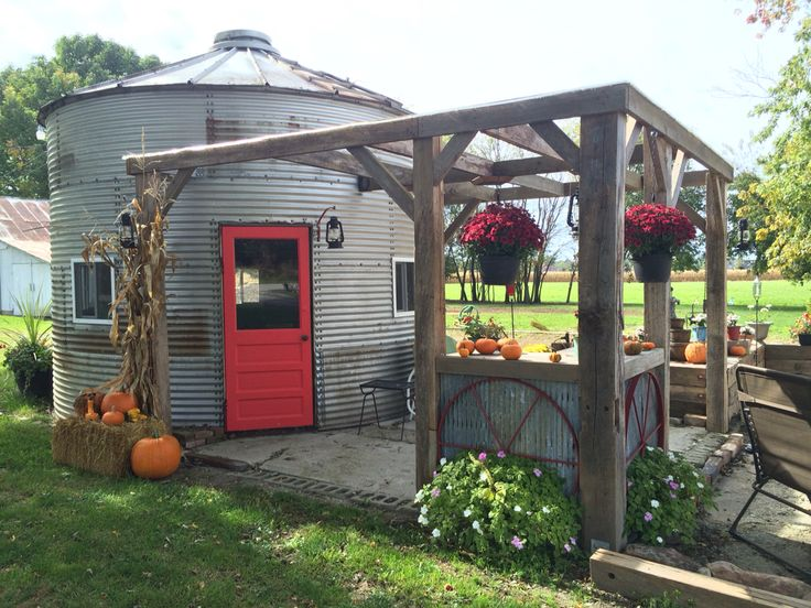 We bought this bin last year from a farmer and dismantled it ourselves in 8 hours and brought it home. Ed reassembled it this spring and used beams from the barn we had to tear down to make the pergola. The old door was here when we moved in and I just painted it red. We love it! / The Green Life <3