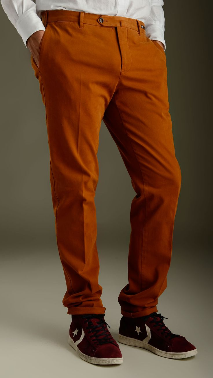 Burnt orange elasticized trousers featuring button and zip fly with button tab, two slant pockets and two back buttoned welt pockets, belt loops, 98% cotton and 2% elastane.