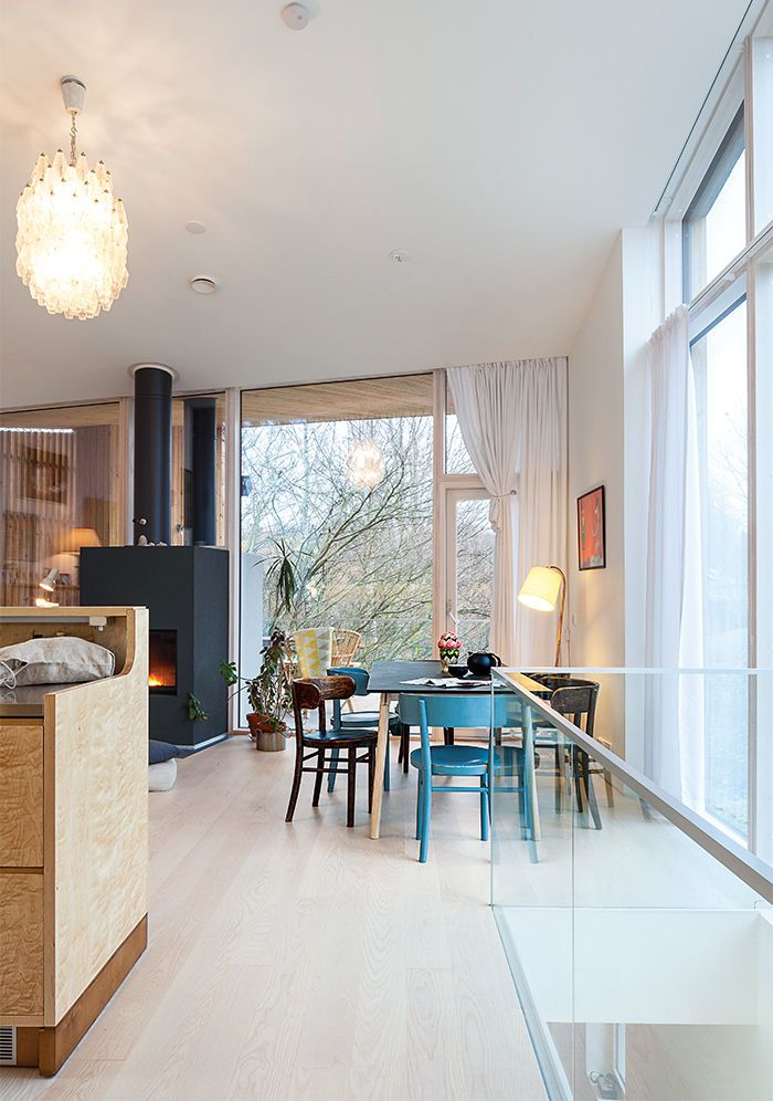 Modern home in Finland with sauna has custom table, chandelier, and dining chairs in the dining area