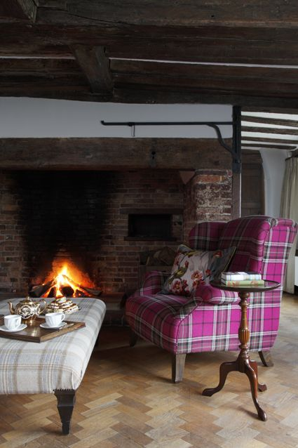 We love the pink tartan armchair in this cosy setting. Perfect quirky comfort in front of a roaring fire. #tartan #upholstery #interior #fireplace