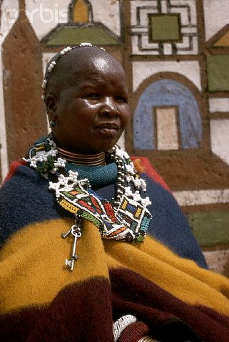 Africa | A traditionally dressed member of the Bantu tribe Ndebele stands in front of a mural in her village. South Africa. | I© Charles & Josette Lenars