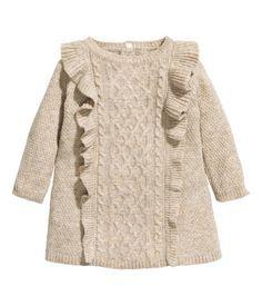 Vestido en punto con textura de mezcla de algodón con lana en la trama. Modelo de manga larga con sección delantera en punto trenzado con ribete de volantes y cierre de botón en la nuca.