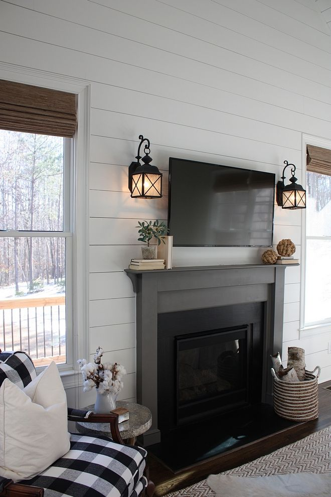 Cute farmhouse living room. Love the contrast between the walls and black fireplace.