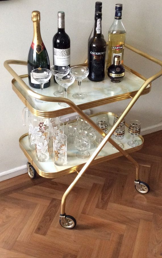 Vintage bar cart drinks trolley folding brass faux marble rolling mid century modern collapsible tea trolley hostess home bar table cabinet  Rare 1960s folding bar cart or trolley. Perfect for serving and storing drinks in a mid century home. This gold tone and marble-like trolley is in excellent vintage condition, it is a slightly smaller sized lightweight cart so rolls away neatly and doesnt take up much room. Folds for storage. Great for cocktails, parties and retro themed events.  Super…