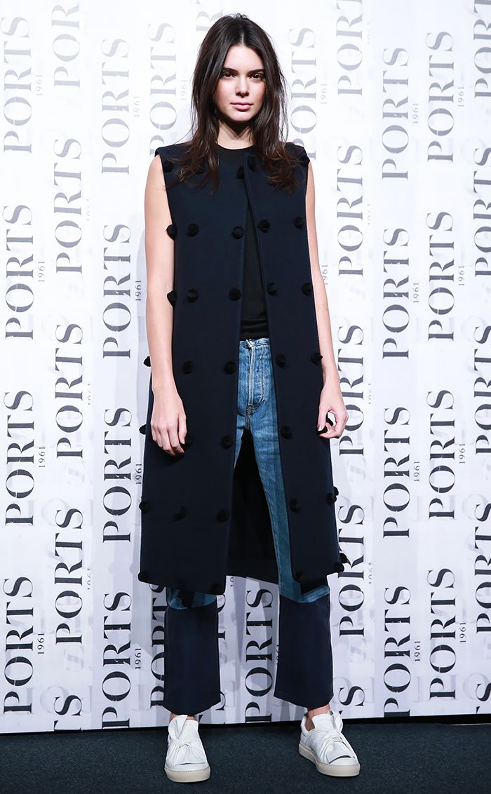 Kendall Jenner wears a black tank top, embellished long vest, cropped jeans, and white sneakers