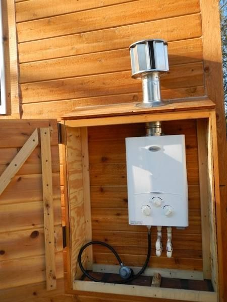 "Tankless Hot Water Heater outside of Tiny house covered by built-in ""shed"" Via steves-tiny-house-for-sale-3"