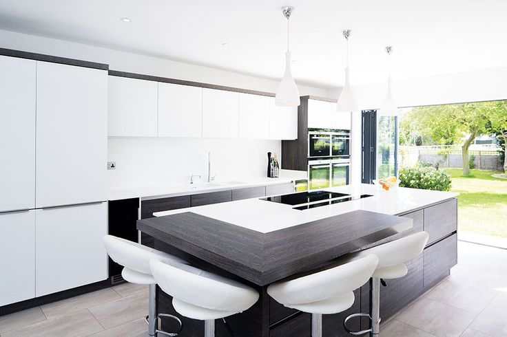 This modern kitchen features a 3m island with a concealed extractor fan, alongside luxuries such as wine fridges, a double oven and Quooker boiling water tap. View Project →