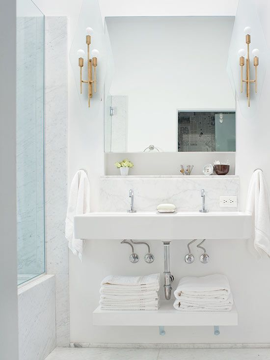 edgy + unexpected: modern brass sconces in a classic white bathroom