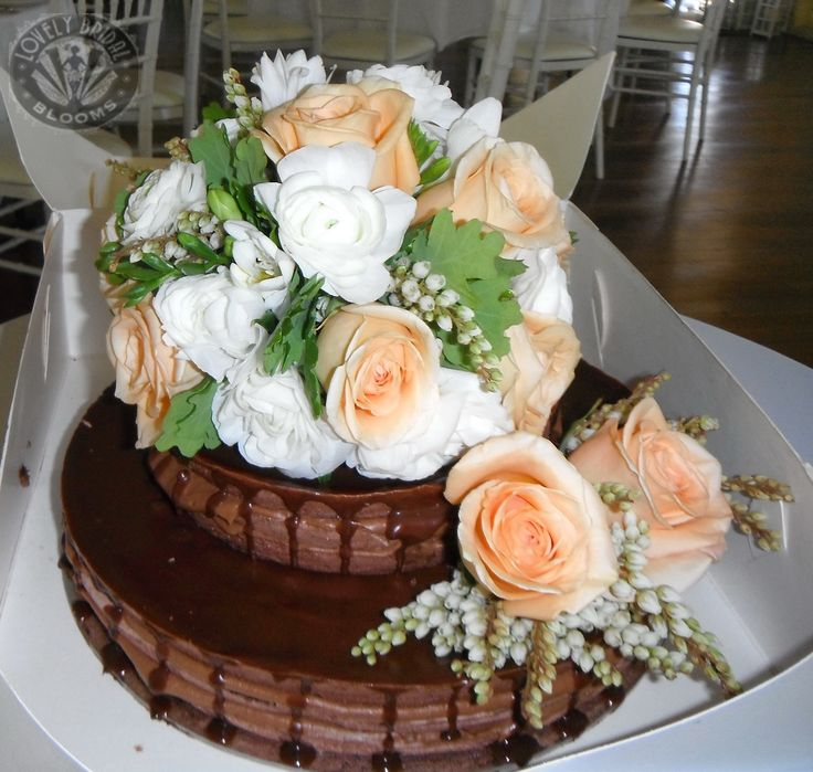large cake topper of roses, ranunculus, and pieris
