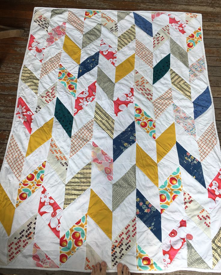Scrappy chevron quilt of half square triangles. Made from our recycled girls clothes, scraps and sheets. Synthetic blanket as batting. Sheet as backing.