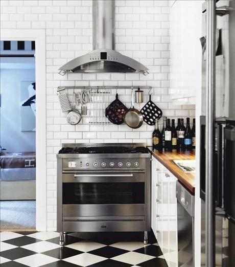 Ett litet men klassiskt kök med rutigt golv, vitt kakel och gasspis   från Ilve. Fläkt från Gaggenau...