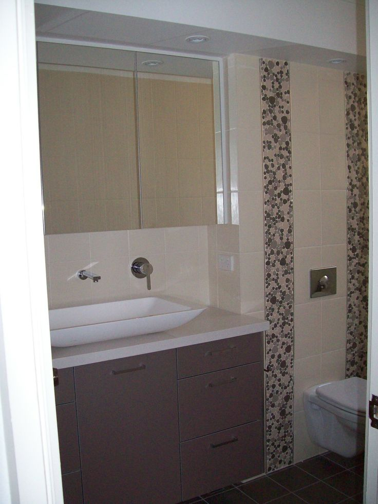 View of vanity and concealed cistern mirror shaving cabinetry with down lights in bulkhead