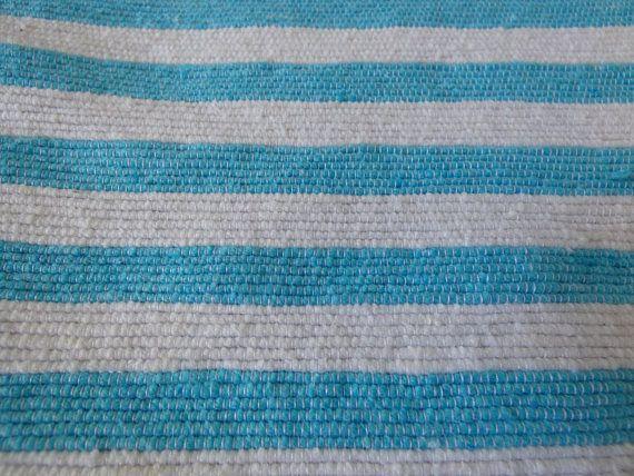 Couverture marocaine en laine avec pompons, 100% laine naturelle filée à la main sur un métier à tisser en bois.  Les pompons faits à la main en laine de mouton organique et les fines rayures turquoises apportent à cette couverture une discrète touche de fantaisie. Elle peut aussi bien être utilisée comme couvre lit, plaid ou jeté de canapé.