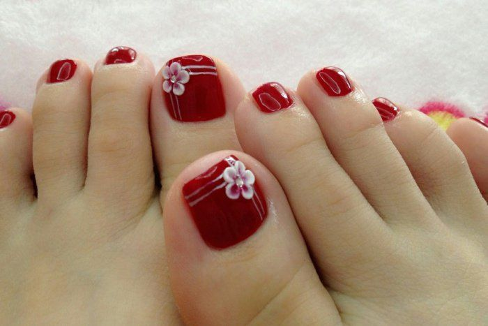 nail art facile: vernis rouge brillant et fleurs blanches