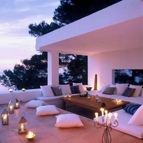 Goed idee van overdekt terras met verlaging voor tafel en banken met kussens op.