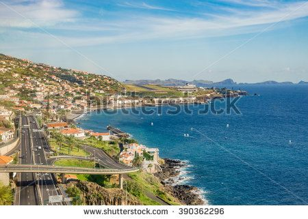 Highway road and traffic along the coast. Coastal freeway road with running cars, beautiful turquoise sea water, island skyline, small town and high cliffs during sunny day with blue sky.