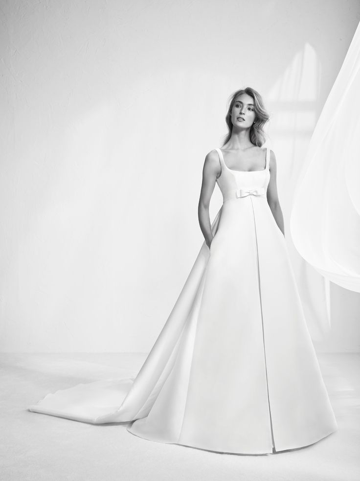 The most classic brides have this fabulous empire-line design in Clementine Mikado with A-line skirt and train overlay on the back. A classic style that accentuates sensuality with its beautiful balconette neckline and bow detail under the bust in the same fabric.