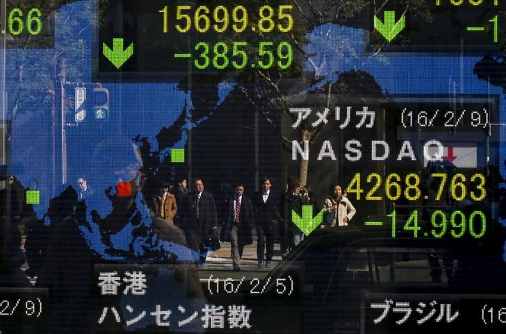 GLOBAL-MARKETS/ People are reflected in a display showing market indices outside a brokerage in Tokyo, Japan, February 10, 2016. Asian stocks dipped early on Wednesday amid growing concerns about the health of the global banking sector, particularly in Europe, while the safe-haven yen stood near a 15-month high versus the dollar. REUTERS/Thomas Peter TPX IMAGES OF THE DAY