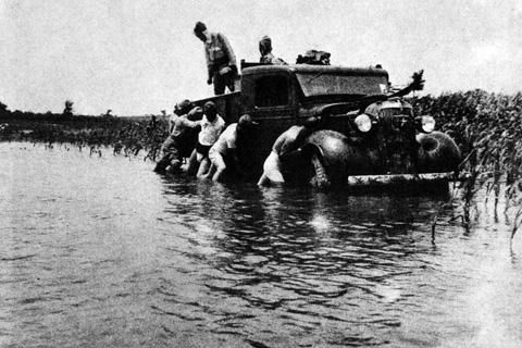 Japanese soldiers slowed down by flooding in China, 1938, possibly as Yellow River dykes are breached.