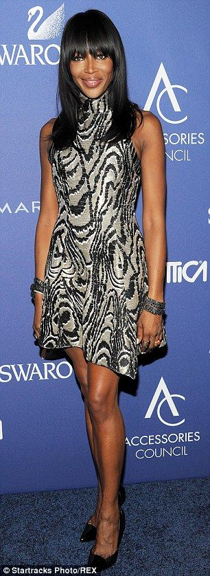 Standing tall: Naomi added height to the proceedings with a classic pair of black heels, w...