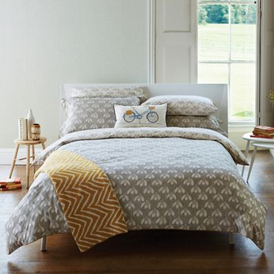 Snow Drop duvet cover featuring an all-over stylised snowdrop flower head, pigment-printed onto a grey ground with the design reflected on the reverse in the contrasting colourway and piped in mustard.
