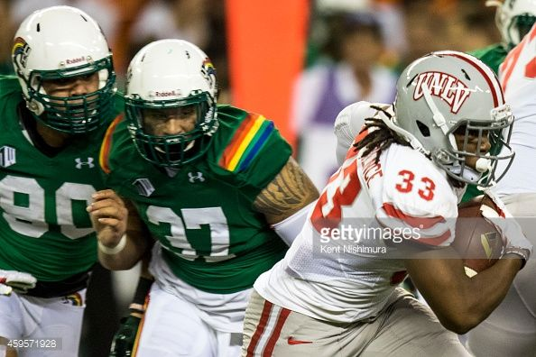 Shaquille MurrayLawrence of the UNLV Rebels carries the ball while being chased by defenders Ammon Barker and Simon Poti of the Hawaii Warriors...