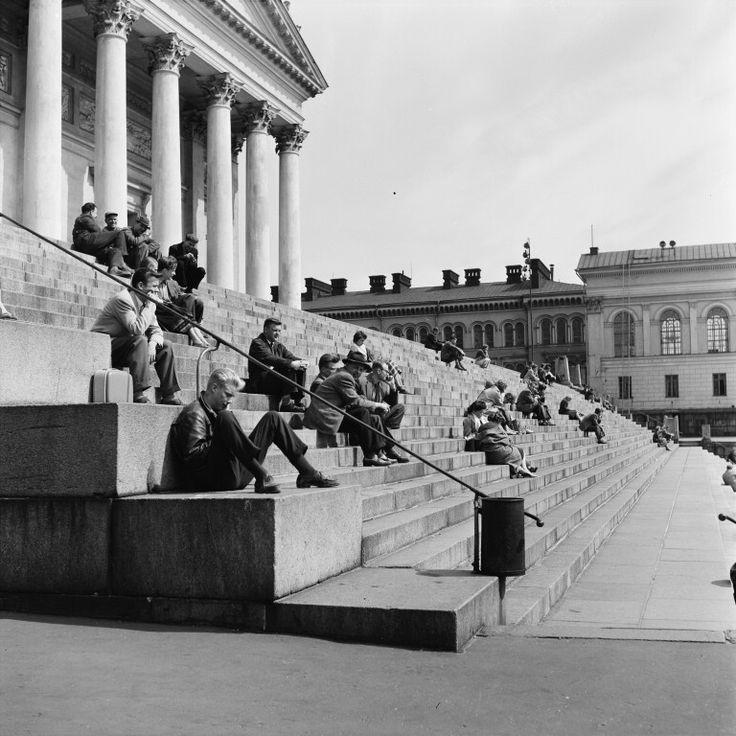 Kaupunkilaisia istumassa Tuomiokirkon portailla. - Finna -...