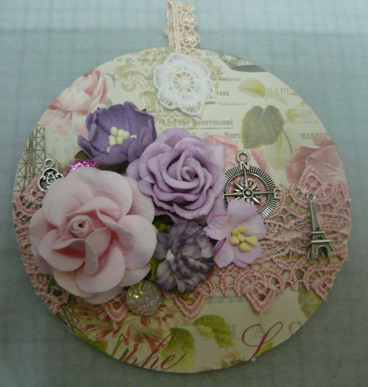 (by Lynne Nye) Altered cd flowers, lace, metal charms, sparkles,
