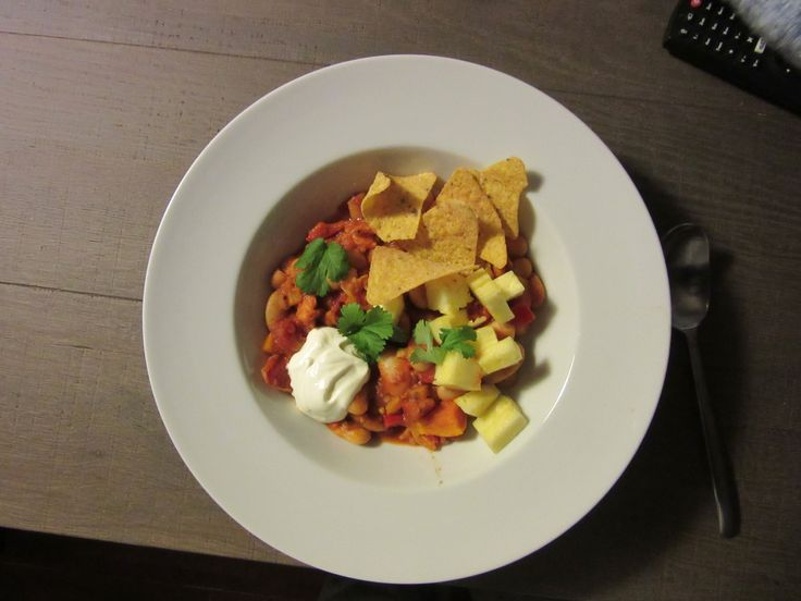 Chili met zoete aardappel, taco chips, zure room en verse ananas