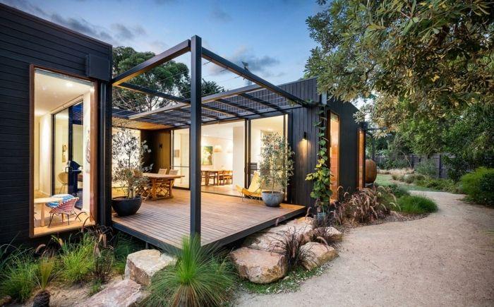 construire une terrasse, façade foncée, salon de jardin en bois, pot à fleur noir, rocher, jardin, sable, arbres