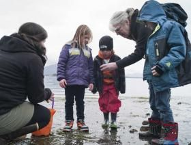 Glacier Valley Elementary School kindergarten teacher Joann Steininger, right, and parent Kayla Tripp help students Aubrey Ridle, left, Alexander Tripp, center, and Parker Henderson learn about what lives in the intertidal zone during Monday's low tide at Auke Recreation Beach.  Michael Penn | Juneau Empire