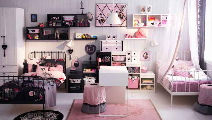 IKEA Kinderzimmer in Schwarz und Weiß; u. a. mit ausziehbaren MINNEN Bettgestellen in Weiß + Schwarzbraun, TROFAST Wandaufbewahrungen in Schwarz + Weiß, TROFAST Regalrahmen mit TROFAST Boxen in Schwarz + Weiß, MICKE Schreibtisch weiß, kurzflorigem RARING Teppich rosa + SKÄRT Hockerbezügen in Rosa
