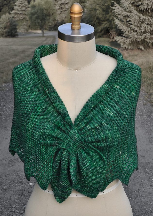 Free knitting pattern for Carol's Clever Little Shawl - Carol Sanders' keyhole shawl was inspired by an antique 1800's shawl. It is knit from side to side in garter stitch with lace edging added as you go. The shawl is shaped with short rows and closes cleverly with interlacing front tips created at the beginning and end of the shawl.