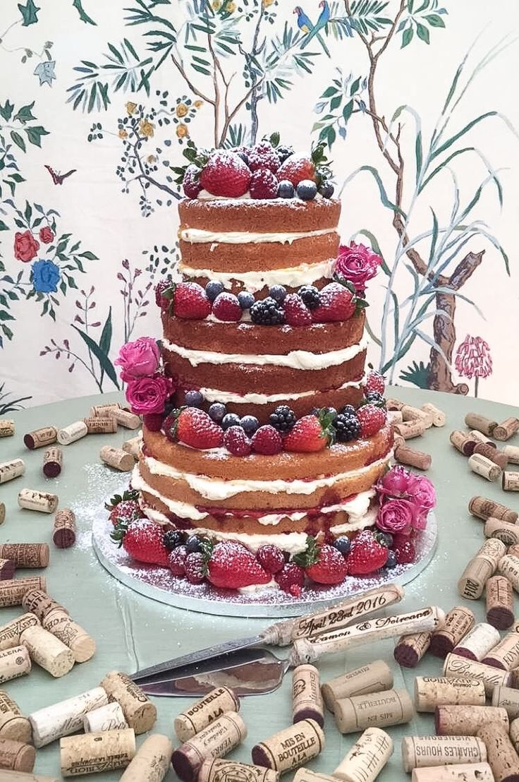 Fresh and luscious 'Naked' cake served in a stunning marquee wedding venue. Dressed with fresh berries and rose buds. Love the use of the corks for display and the beautiful hand carved cake serving set.