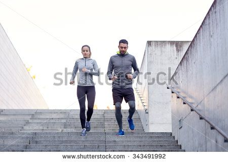 fitness, sport, exercising, people and lifestyle concept - couple walking downstairs on stadium - stock photo