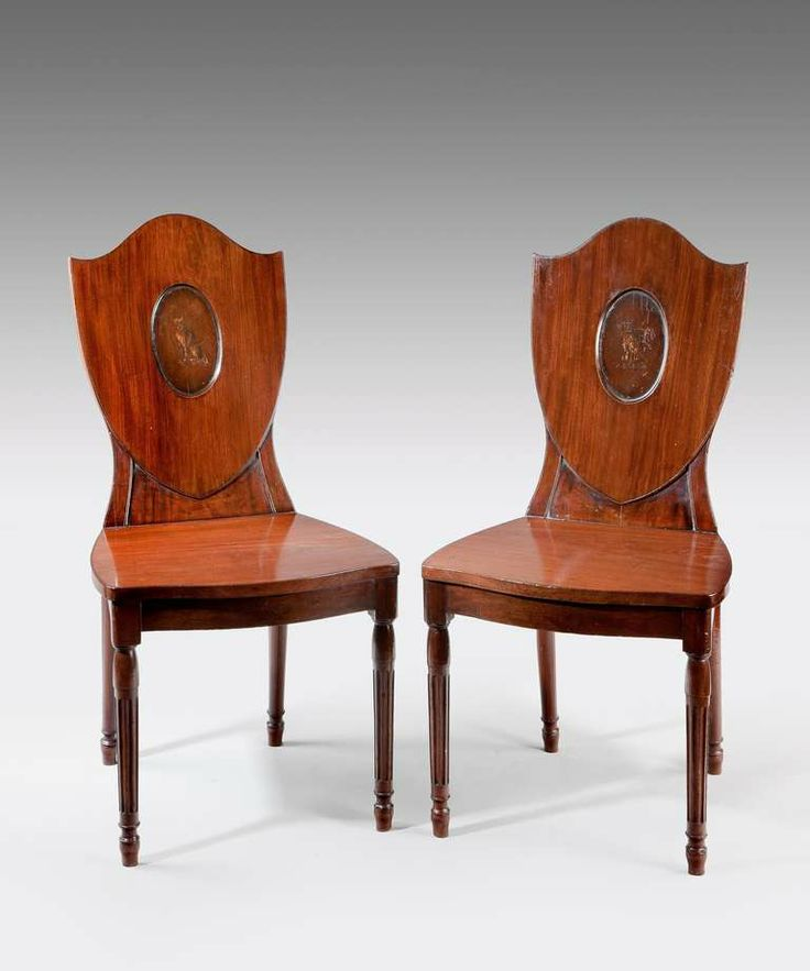 These are George III Hepplewhite mahogany hall chairs. Notice the shield back design used by Hepplewhite. The chairs are decorated with an English family crest. The legs are reeded and tapered.