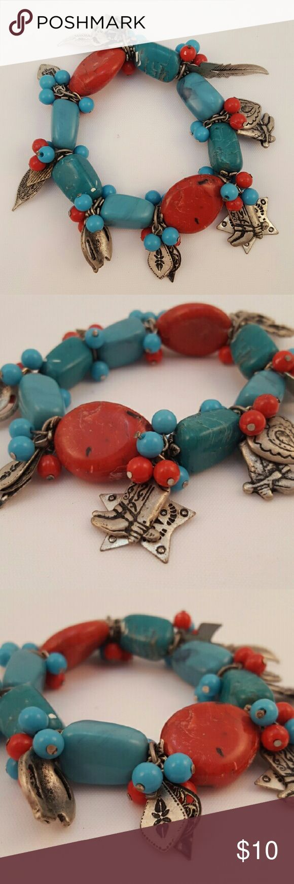 Indian style bracelet. Costume jewelry Indian design costume jewelry bracelet. Turquoise type beads in red and turquoise with lots of dangling charms that include boots, feather, cross, heart, horseshoe, and more. unknown Jewelry Bracelets