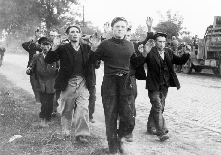 World War II: The Invasion of Poland and the Winter War. Several civilian prisoners of war, with arms raised, walk along a road during the German invasion of Poland in September of 1939. (LOC)