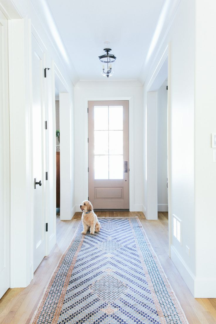 """The crisp white walls of this simple entry way are a gorgeous contrast to the detailed blue tiled """"runner"""" on the floor."""