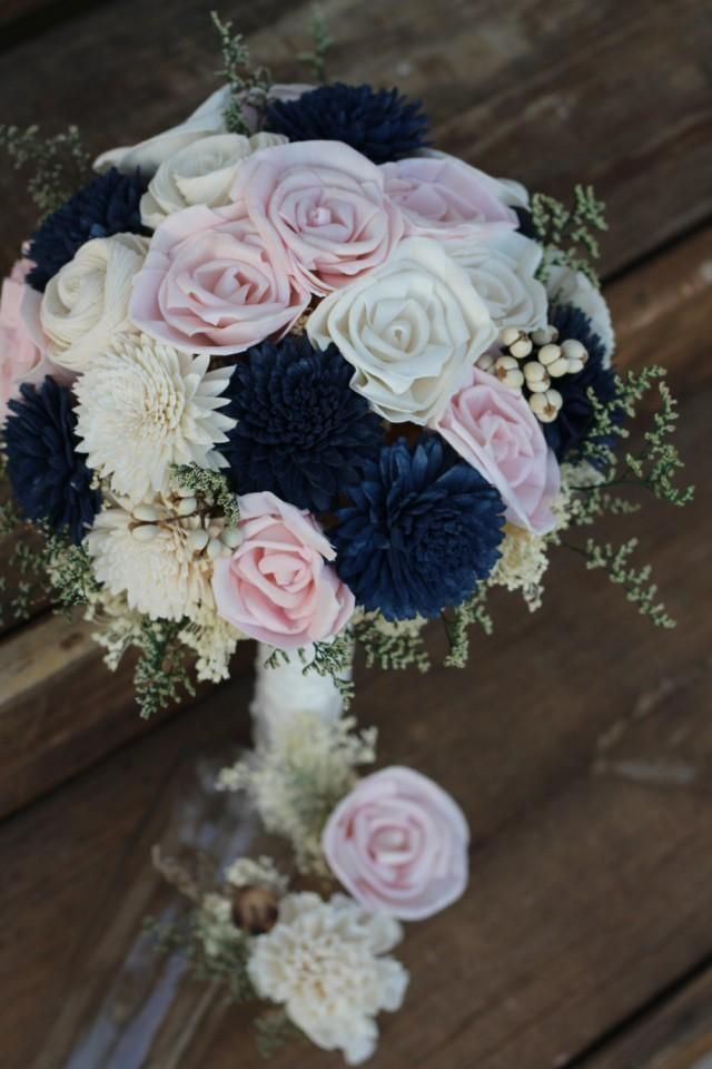 Thanks for looking. I hope to work with you on your floral needs. This listing features a bouquet featuring light pink sola rose buds, navy blue zinnias and roses in a creamy ivory color. It is accented with soft, supple caspia and tallow berries.  Gorgeous! This bouquet has cream filler and is wrapped in cream fabric and accented with a lace collar with pearls. Please note, Any of these flower colors may be hand dyed in your very special wedding palette colors. The picture above shows a…