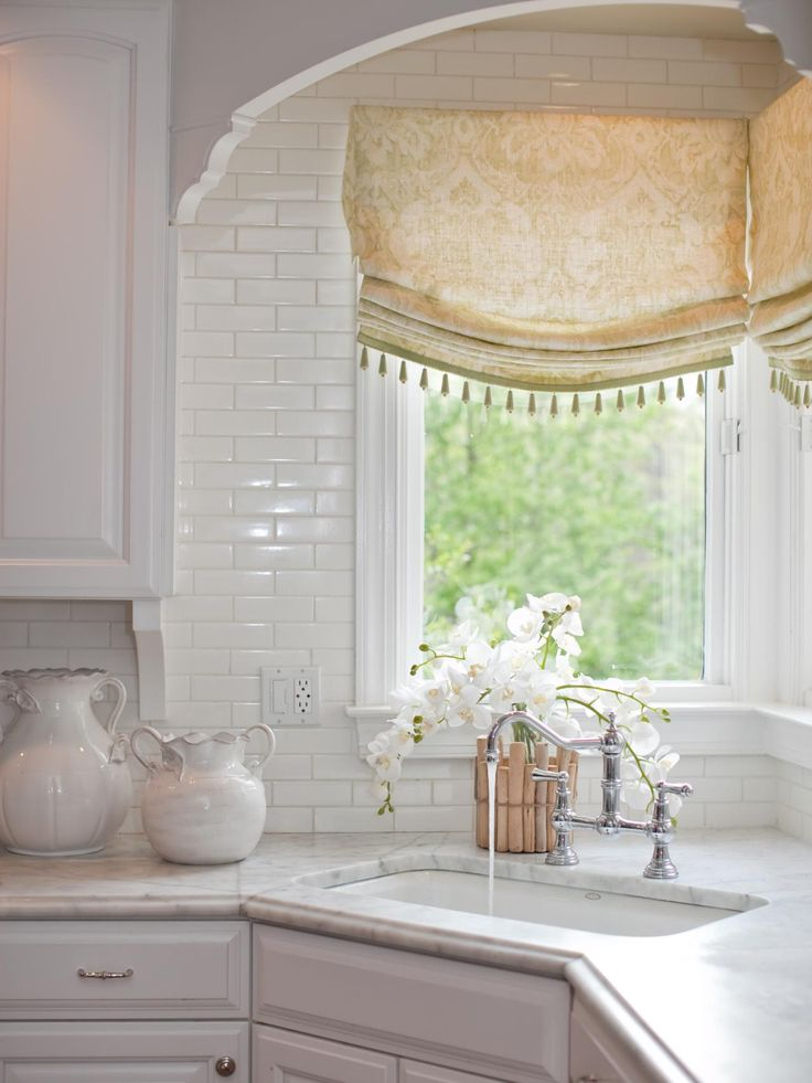 A corner sink takes center stage in this white traditional kitchen. Beaded Roman shades add color and style, along with a bridge faucet and a graceful orchid.