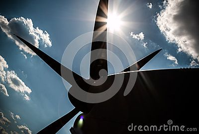 Blue sky clouds and trails. Blue background. Silhouette of an airplane. Sun rays.
