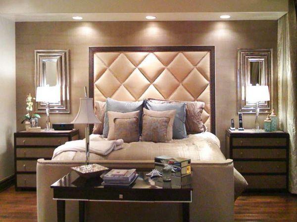 une tête de lit haute, couleur pêche au cadre marron, deux commodes de chevet avec deux lampes jolies et deux miroirs à un encadrement élégant