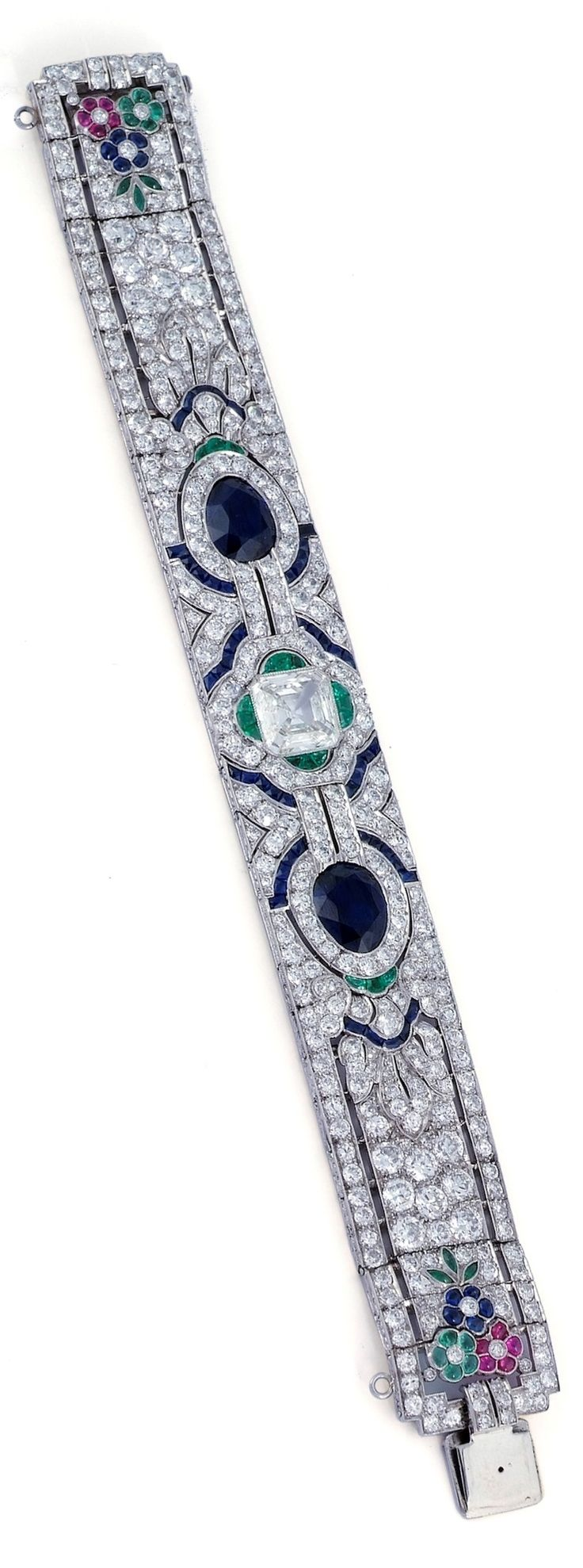 GATTLE - An Art Deco emerald, sapphire and diamond bracelet, circa 1929. Designed as a central emerald-cut diamond weighing 3.73 carats, flanked by two pear-shaped sapphires weighing 8.45 carats, within a pavé-set diamond band with calibré-cut emerald and sapphire accents, embellished to each end with a cabochon gem-set floral cluster, signed Gattle, made by Oscar Heyman. #Gattle #OscarHeyman #ArtDeco #bracelet