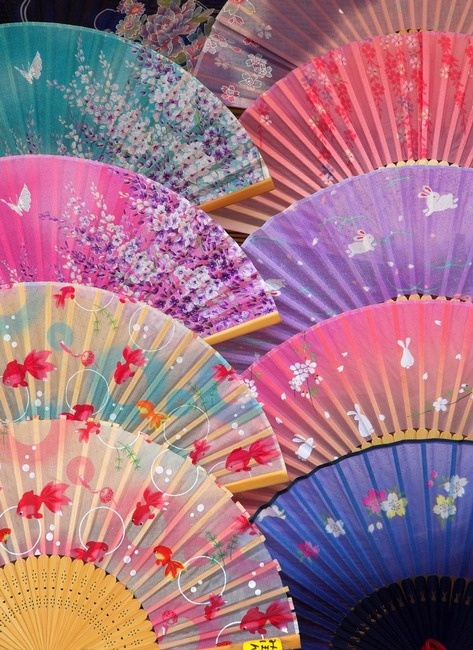 Japanese Hand Fans - the folding fan was invented in Japan in the 8th century and taken to China in the 9th century. They're used by warriors, actors, and children, given as presents, serve as trays for holding gifts, and used in religious ceremonies. The top of the fan handle symbolizes the beginning of life; the ribs symbolize the roads of life going out in all directions to good fortune.