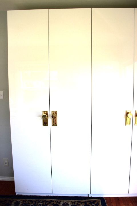 Emily Henderson, white glossy lacquer ikea pax wardrobes with vintage brass hardware.